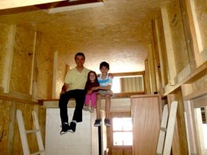crianças e pai na casa pequena em construção
